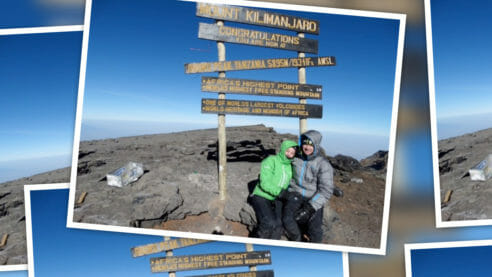 Photo of a woman and partner weaing warm winter clothing posing in front of waypoint sign indicating they are on Mount Kilimanjaro